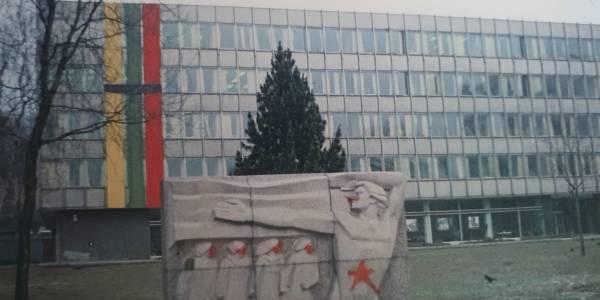 """Gedulo juosta perjuosta trispalvė ant tuometinio """"Miestprojekto"""" pastato. Stela spontaniškai apterliota raudonomis žvaigždėmis, simbolizuojančiomis sovietinę sistemą ir sovietinę kariuomenę."""